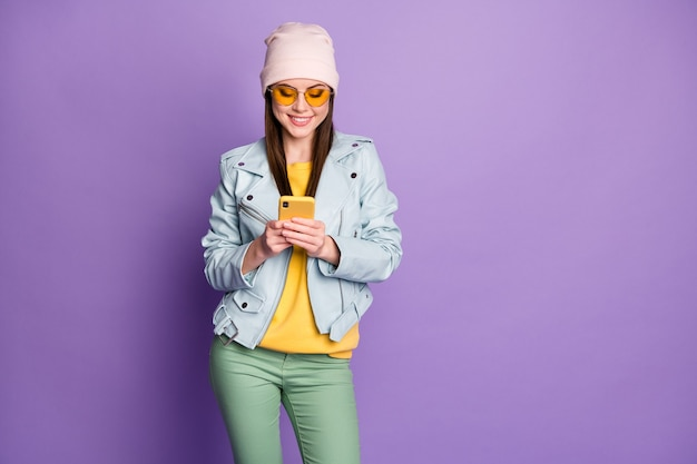 Foto von coolen, stylischen, hübschen lady street look-kleidung halten telefongespräche mit einem lächeln auf den lippen tragen sonnenbrillen freizeithut blaue jacke gelber pullover grüne hose isoliert lila farbhintergrund