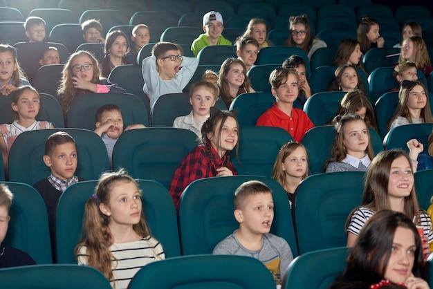 Foto von den lustigen kindern, die film im kino aufpassen.