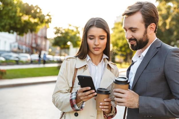 Foto von denkenden büroangestellten, mann und frau in formeller kleidung, die kaffee zum mitnehmen halten, während sie das handy auf der stadtstraße benutzen using