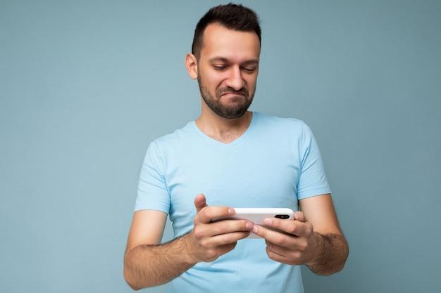 Foto von der frage eines gutaussehenden jungen mannes mit bart, der ein blaues t-shirt trägt, das auf blauem hintergrund isoliert ist und die mobiltelefonkommunikation online im internet mit blick auf das gadjet-display hält und nutzt.
