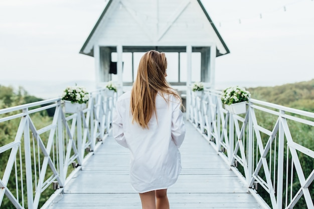 Foto von der rückseite. am frühen morgen sommerterrasse im resort. frau im weißen hemd gehen.