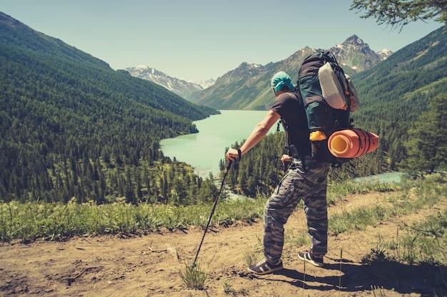 Foto von der rückseite des touristenmannes mit gehstöcken mit den händen auf einem berghügel in der nähe des sees. touristische haltestöcke für nordic walking.