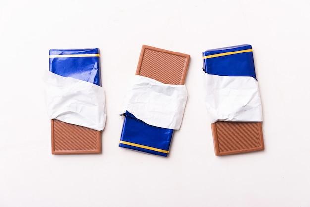 Foto von drei tafeln der schmackhaften schokolade im blauen papier auf weißem tisch