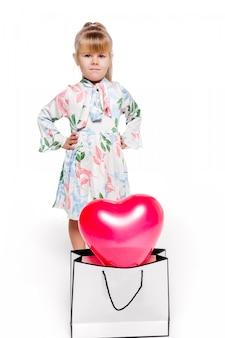 Foto von ein kleines modisches mädchen in einem weißen kleid mit einem blumendruck steht neben einem großen paket mit einem herzförmigen ballon im inneren