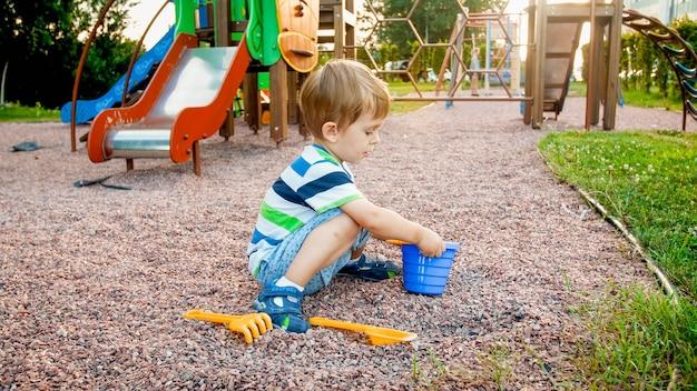 Foto von einem entzückenden 3-jährigen kleinen jungen, der auf dem spielplatz sitzt und mit einer kleinen plastikschaufel und einem eimer sand gräbt