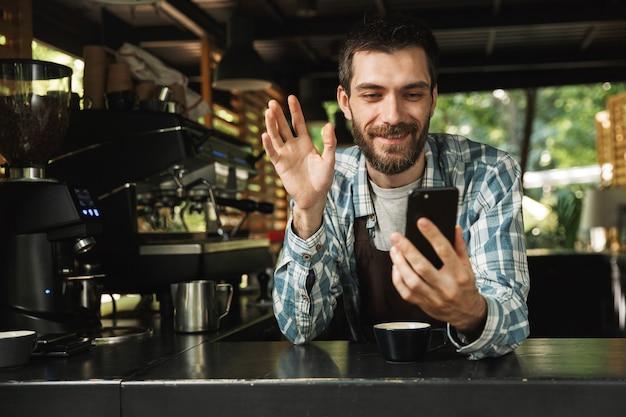 Foto von einem glücklichen barista, der eine schürze trägt und lächelt, während er das smartphone im café oder kaffeehaus im freien benutzt