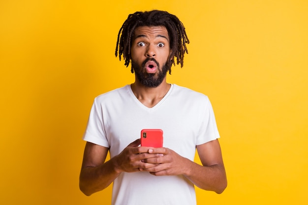 Foto von einem schwarzen mann, der eine telefonkamera hält, schockiert ausdruck, ein weißes t-shirt tragen, isoliert, gelber farbhintergrund