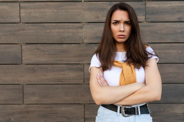 Foto von empfindlicher trauriger verärgerung beleidigte verärgerte junge brunet-frau, die ein lässiges weißes t-shirt und jeans mit gelbem pullover trägt, der in der nähe der braunen wand auf der straße steht.