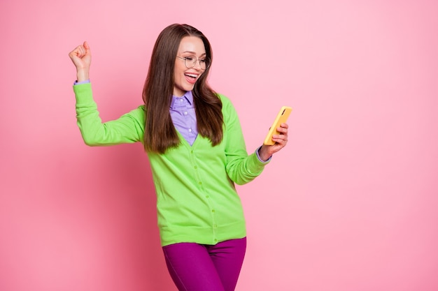 Foto von entzücktem mädchen, das smartphone verwendet, um fäuste zu heben, schreien, hemdhosenhosen tragen, isoliert pastellfarbener hintergrund