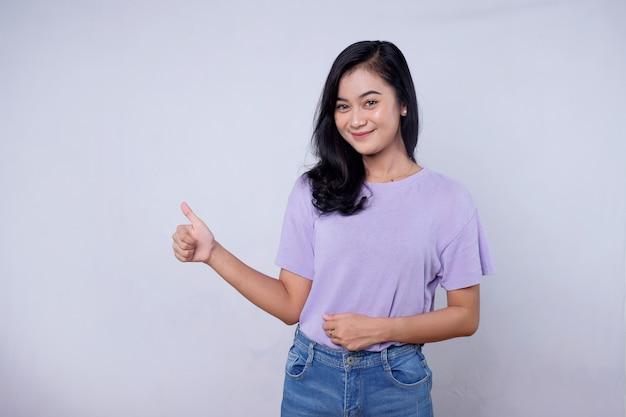 Foto von erfreuter fröhlicher asiatischer frau, zeigt weg, zeigt leerzeichen, freut sich, artikel zum verkauf zu bewerben