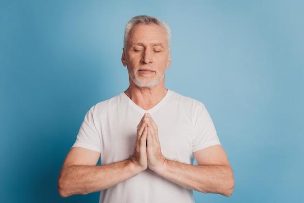 Foto von ernsten alten mann betet hände auf blauem hintergrund isoliert
