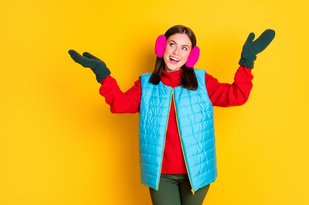 Foto von erstauntem aufgeregtem mädchen, das hand fängt, luftfliegen, schneeflocken, kopienraum, blau, rosa saisonkleidung, einzeln auf hell glänzendem hintergrund tragen