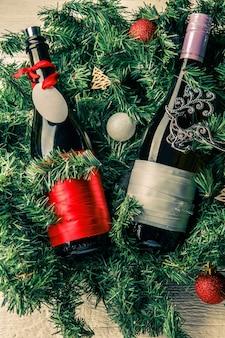 Foto von fichtenzweigen mit zwei flaschen wein, leere grußkarte, weihnachtsspielzeug auf weißem tisch