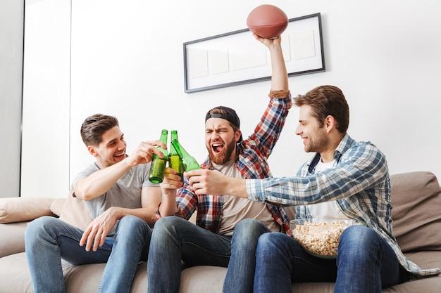 Foto von freudigen männern, die schreien und flaschen bier klirren, während sie den sieg der lieblingsfußballmannschaft zu hause feiern