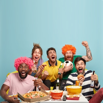 Foto von freunden fußballspiel schauen, tor feiern, fäuste ballen, sportwettkampf genießen, leckeren snack haben, kaltes bier trinken, freizeit zu hause verbringen. zeitvertreib und unterhaltung
