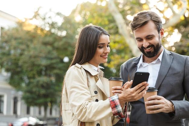 Foto von fröhlichen büroangestellten, mann und frau in formeller kleidung, die kaffee zum mitnehmen halten, während sie das handy auf der stadtstraße benutzen?
