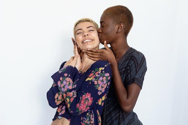 Foto von fröhlichen damen, die zusammengehörigkeit küssen und umarmen, unterschiedlicher rassen sind und in freizeitkleidung gekleidet sind.