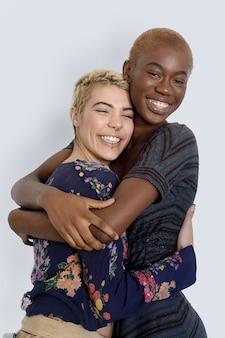 Foto von fröhlichen damen umarmen und genießen die zweisamkeit, die unterschiedlicher rassen sind, in lässigen pullovern gekleidet sind, isoliert auf weißem hintergrund. diverse frauen lachen glücklich, haben spaß zusammen.