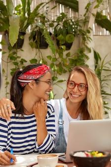 Foto von fröhlichen frauen bereiten sich auf die prüfungssitzung vor, erledigen gemeinsam hausaufgaben, schreiben in ein notizbuch, genießen kaffee