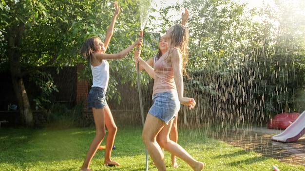 Foto von fröhlichen, fröhlichen mädchen in nasser kleidung, die unter wassergartenschlauch tanzen und springen. familie, die im sommer im freien spielt und spaß hat