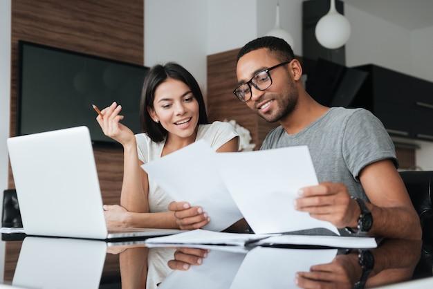 Foto von fröhlichen, liebevollen jungen paaren, die laptop verwenden und ihre finanzen mit dokumenten analysieren. schauen sie sich papiere an.