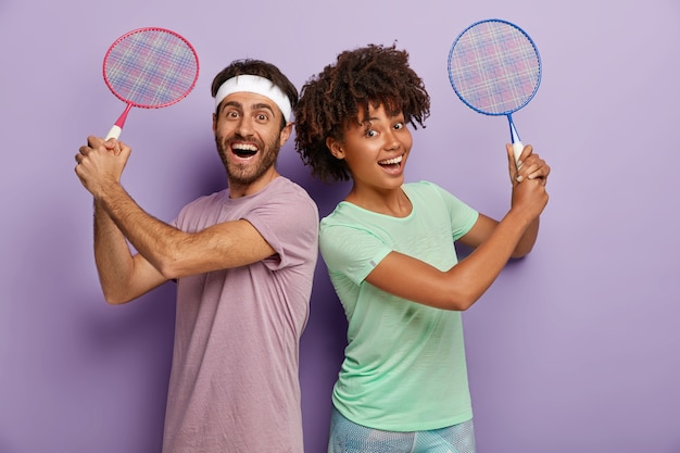 Foto von fröhlichen mischlinge frau und mann treten zurück, halten tennisschläger, genießen das spielen, lachen positiv, in t-shirts gekleidet, aktiv und zufrieden
