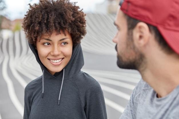 Foto von fröhlichen teenagern in modischen kleidern, die in hochstimmung sind, haben eine angenehme zeit zusammen