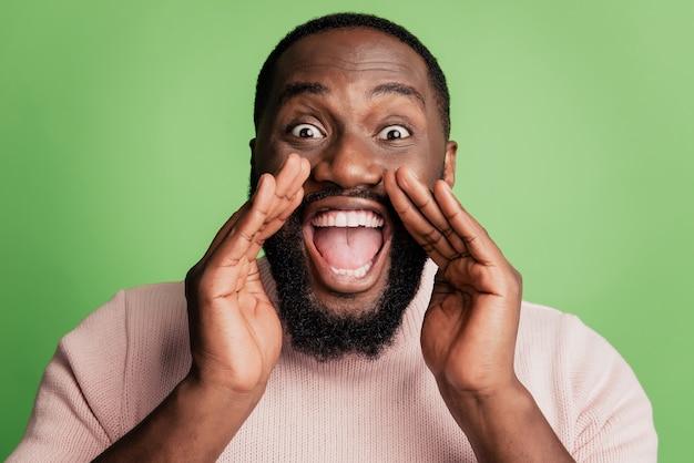Foto von fröhlichen verrückten aufgeregten kerl mit offenem mund halten palmen schreien nachricht tragen weißes hemd über grünem hintergrund