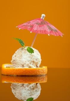 Foto von geschnittener orange mit eis und minze darauf. geringe schärfentiefe