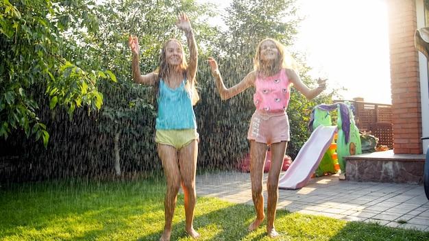 Foto von glücklich lachenden kindern in nasser kleidung, die unter warmem regen im garten springen und tanzen. familie, die im sommer im freien spielt und spaß hat