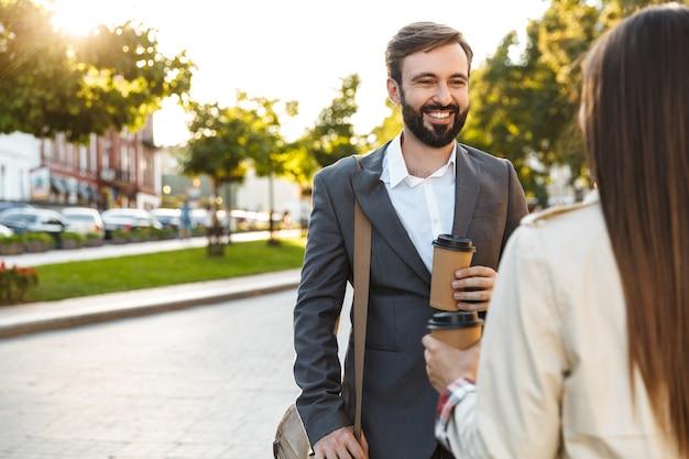 Foto von glücklichen büroangestellten, mann und frau in formeller kleidung, die kaffee zum mitnehmen trinken, während sie auf der stadtstraße sprechen