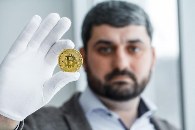 Foto von goldenen bitcoin virtuellen münzen in einer hand
