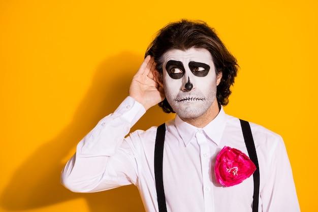 Foto von gruseligen zombie-borsten-mann-hand-ohr-interessenten belauschen geister private verschwörung tragen weißes hemd rose zuckerschädel-tod-kostüm-hosenträger isoliert gelber hintergrund