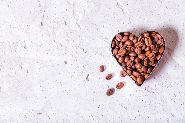Foto von herzförmigen kaffeebohnen kopieren raum auf konkretem hintergrund. horizontales foto. draufsicht
