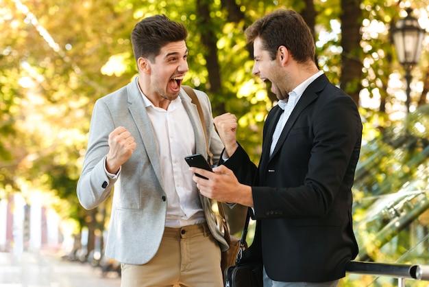 Foto von hübschen unternehmern in anzügen, die smartphone verwenden, während im freien durch grünen park mit kaffee zum mitnehmen, während des sonnigen tages gehen