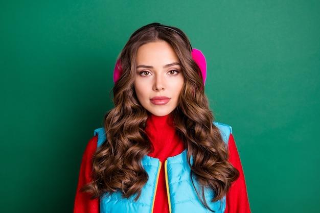 Foto von hübscher charmanter junger dame ruhig fokussierter gleichgültiger blick beim betrachten des winterwetters durch das fenster tragen rosa ohrwärmer blaue weste roter pullover isoliert grüner farbhintergrund
