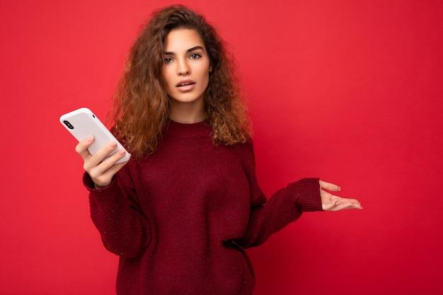 Foto von hübscher fragender verärgerter junger frau mit lockigem haar, die einen dunkelroten pullover trägt, der auf rotem hintergrund isoliert ist und das handy in die kamera schaut und nicht versteht