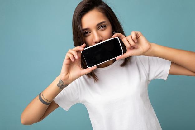 Foto von hübscher positiver junger brünetter frau, die gut aussieht und weißes t-shirt trägt, das isoliert auf steht
