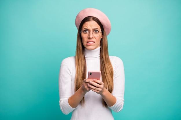 Foto von hübscher verängstigter dame, die telefon hält, neuen beitrag lesen negative kommentare beißende lippen tragen spezifikationen moderne rosa baskenmütze weißer rollkragen isoliert heller blaugrüner farbhintergrund