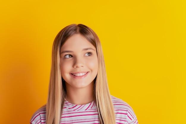 Foto von inspiriertem kind mädchen denken look copyspace über gelbem hintergrund