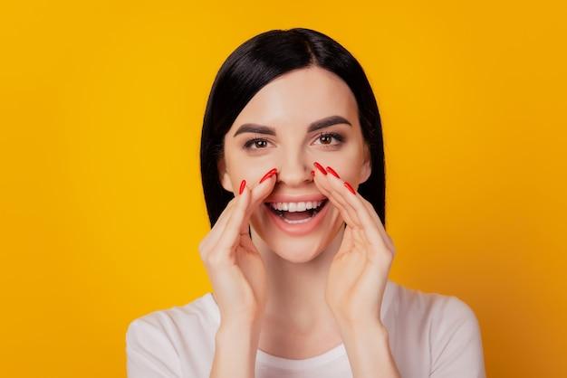 Foto von jungen attraktiven frauenhänden in der nähe des mundes sagen nachrichten schreien ankündigung isoliert auf gelbem hintergrund