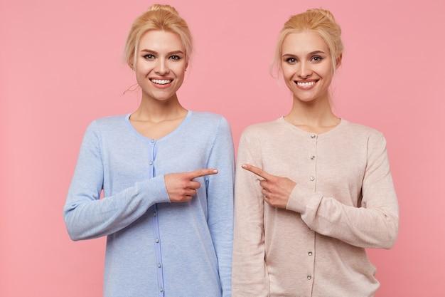Foto von jungen breit lächelnden glücklichen blonden zwillingen, die auf einander lokalisiert über rosa hintergrund zeigen.