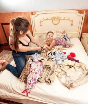 Foto von kämpfender älterer und jüngerer schwester im schlafzimmer