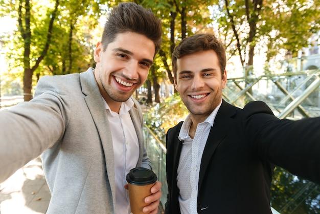 Foto von kaukasischen geschäftsleuten in anzügen, die selfie-foto auf smartphone nehmen, während im freien durch grünen park mit kaffee zum mitnehmen gehen