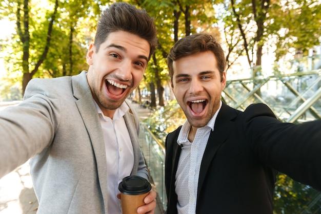 Foto von kaukasischen geschäftsmäßigen männern in anzügen, die selfie-foto auf smartphone machen, während im freien durch grünen park mit kaffee zum mitnehmen gehen
