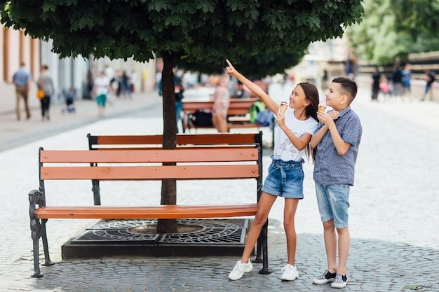 Foto von kinderfreunden, die in der nähe der bank bleiben und zusammen süßes eis essen