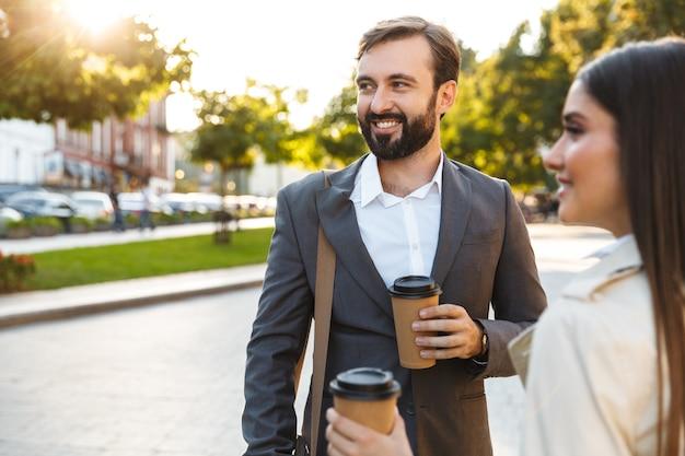 Foto von lächelnden büroangestellten, mann und frau in formeller kleidung, die kaffee zum mitnehmen trinken und beiseite schauen, während sie auf der stadtstraße sprechen?