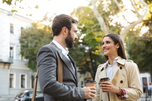Foto von lächelnden büroangestellten, mann und frau in formeller kleidung, die kaffee zum mitnehmen trinken, während sie sich auf der stadtstraße treffen?