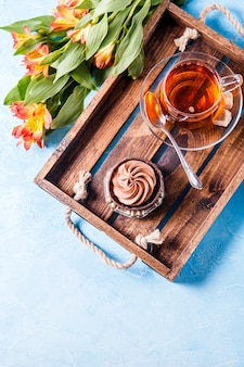 Foto von leichtem frühstück, schwarzem tee, cupkake mit sahne und orange blumen auf holztablett
