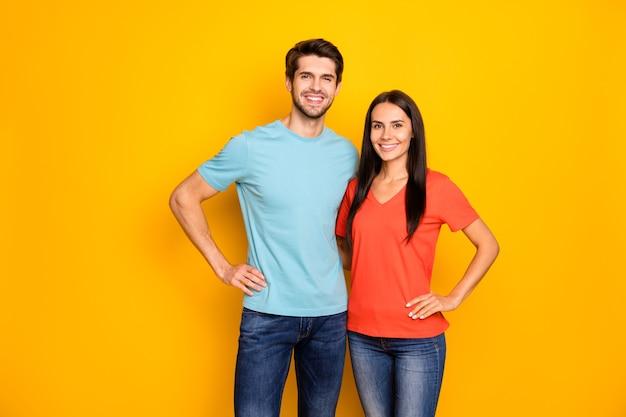 Foto von lustigen reizenden zwei personenpaar kerl und dame, die hände an den seiten umarmen ein bestes team tragen lässige blau-orange t-shirts jeans, die über gelber farbwand isoliert sind